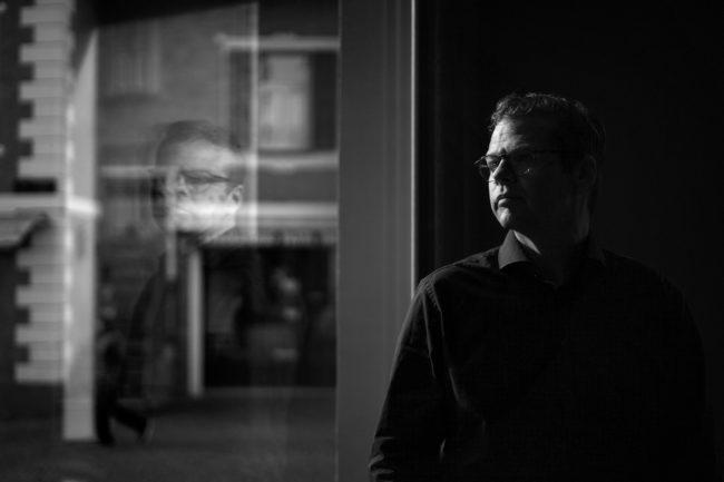 Sort/hvid billede af Anders langballe, der kigger ud af vindue.