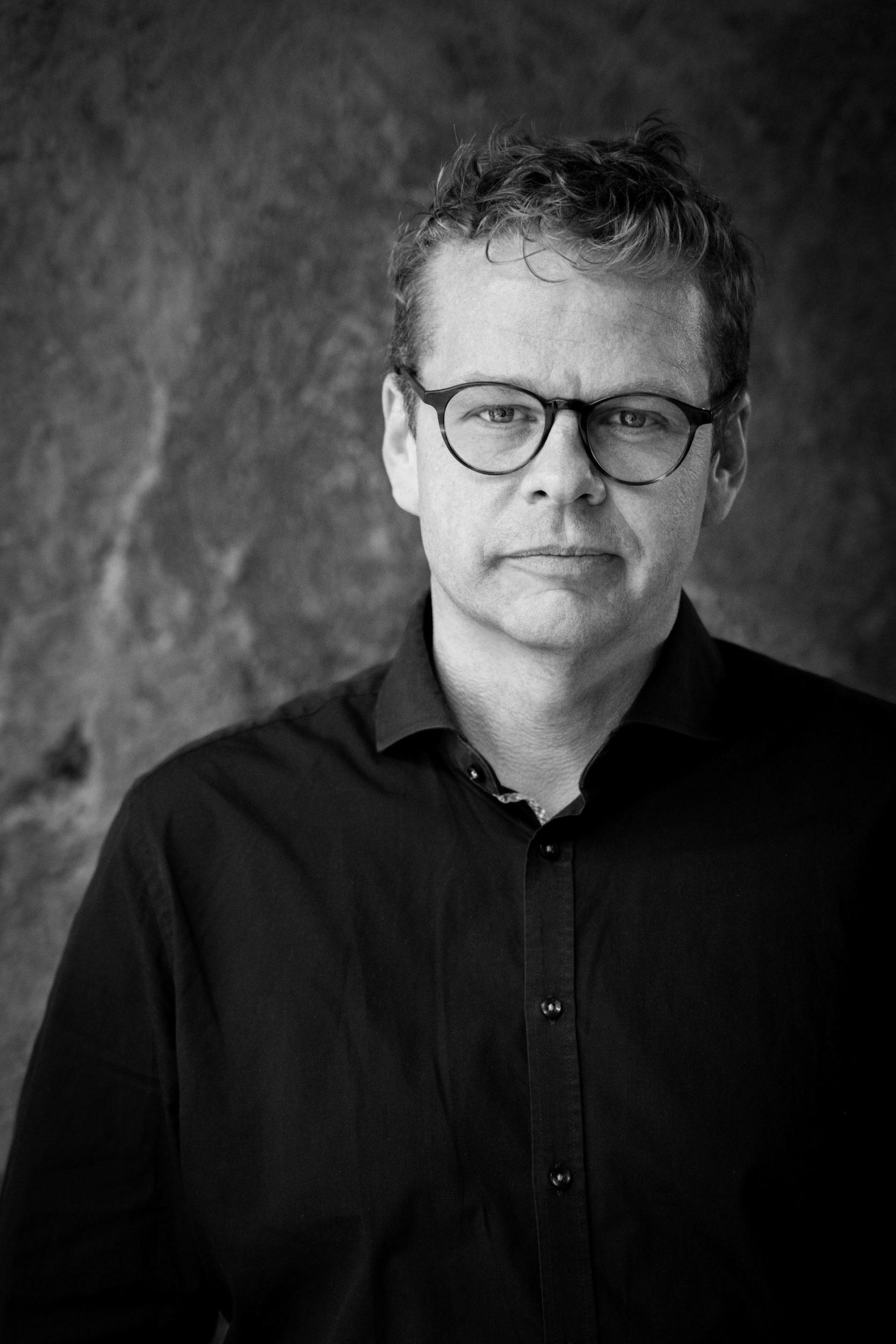 Sort/hvid billede af Anders Langballe, der kigger lige i kameraet.