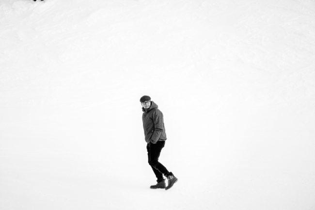Sort/hvid portræt af Anders Langblle, der går kun omgivet af sne.