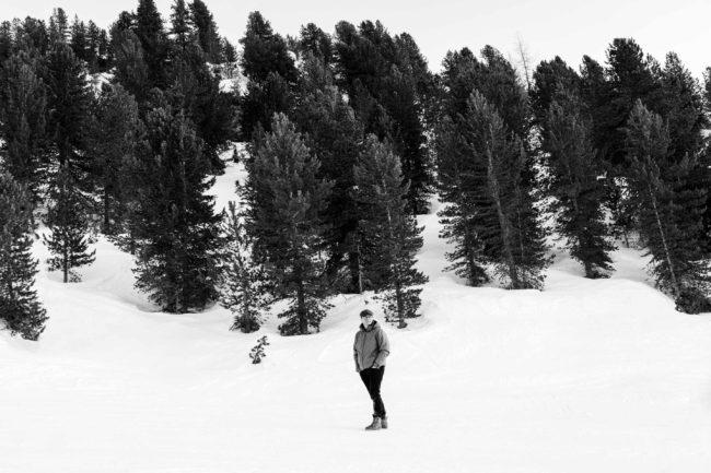 Sort/hvid portræt af Anders Langballe, der står i den hvide sne foran store træer.